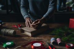 包裹书的妇女当圣诞节礼物 免版税库存照片