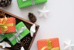 包裹和包装圣诞节和新年礼物的过程 箱子,丝带,锥体,在白色背景的星 库存图片