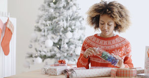 包裹圣诞节礼物的可爱的少妇 免版税库存照片