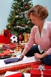 包裹圣诞节礼物的妇女。 免版税图库摄影