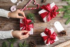 包裹圣诞节礼物的妇女在木桌上 库存图片