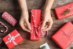 包裹圣诞节礼物的妇女在木桌上 图库摄影