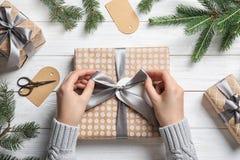 包裹圣诞节礼物的妇女在木桌上 库存照片