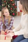 包裹圣诞节礼物盒的女孩 免版税图库摄影