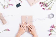 包裹在一张白色桌上的女性手节日礼物 库存照片
