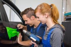 包裹在五颜六色的箔或影片的汽车专业包裹的车门把柄 免版税图库摄影