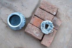 包裹在圈子,在一灰色backgro的一块蓝色金属圆的罐、橙色和棕色长方形砖一起放置和一块白色旧布 图库摄影