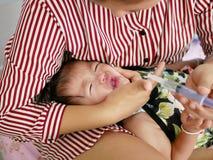 包裹在她哭泣的女婴` s面孔附近的亚洲母亲` s胳膊迫使婴孩采取液体医学 库存照片