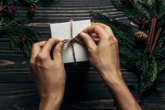 包裹在时髦土气木的手圣诞节简单的礼物 库存照片