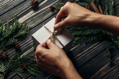 包裹在时髦的鲁斯的手圣诞节简单的当前栓的弓 免版税库存图片
