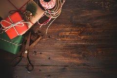 包裹在木桌背景的圣诞节礼物 库存照片