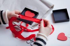 包裹在箱子的白色白种人手心形的玩具在wo 免版税库存图片