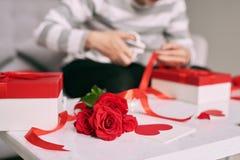 包裹在纸的男性手华伦泰手工制造礼物与红色 免版税库存图片