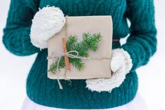 包裹在羊毛制手套的圣诞节牛皮纸礼物 免版税库存图片