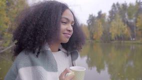 包裹在羊毛格子花呢披肩和喝热的茶的逗人喜爱的黑人女孩 影视素材