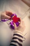 包裹在美妙的白色白种人手心形的玩具 免版税库存照片