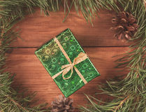 包裹在绿皮书在绿色圣诞树的礼物盒分支和锥体 被定调子的图象 免版税图库摄影