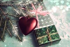 包裹在说谎在他们的心脏的发光的纸礼物 葡萄酒处理 库存照片