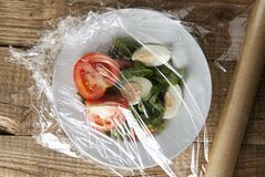 包裹在vegetabes板材的塑料舒展影片卷  在木背景隔绝的特写镜头 没有塑料概念 零我们 免版税库存照片