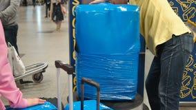 包裹服务在机场,行李的行李在玻璃纸被包装紧贴影片 工作者包裹了很大数量 影视素材