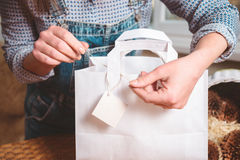 包裹礼物和标记,妇女手做 库存图片