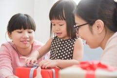 包裹礼物盒的愉快的亚洲家庭 库存图片