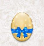 包裹蓝色弓的复活节光滑的鸡蛋 免版税库存图片