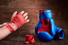 包裹他的有绷带的手和在木板条的嬉戏人拳击手套 免版税库存照片