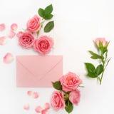 包围与白色卡片和玫瑰色背景 顶视图 平的位置 免版税图库摄影