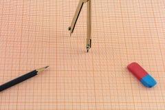 包围橡皮擦和一支铅笔在座标图纸一张  库存图片