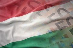 匈牙利的五颜六色的挥动的国旗欧元金钱钞票背景的 图库摄影