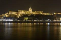 匈牙利的王宫在布达佩斯,在多瑙河上在晚上 免版税库存图片