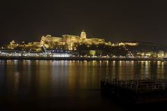 匈牙利的王宫在布达佩斯,在多瑙河上在晚上 免版税库存照片