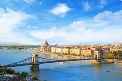 匈牙利议会和铁锁式桥梁的美丽的景色在布达佩斯在晚上,匈牙利全景  库存照片