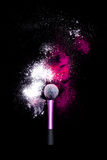 化妆与五颜六色的粉末的刷子在黑背景 爆炸与明亮的颜色的星团 白色和桃红色粉末红色 图库摄影