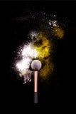 化妆与五颜六色的粉末的刷子在黑背景 爆炸与明亮的颜色的星团 白色和黄色粉末 图库摄影