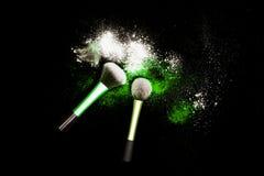 化妆与五颜六色的粉末的刷子在黑背景 爆炸与明亮的颜色的星团 白色和绿色粉末 库存图片