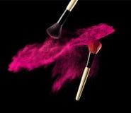 化妆与桃红色粉末爆炸的刷子在黑背景 库存照片