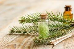 化妆云杉的油和盐在瓶有毛皮分支的在木桌背景 免版税图库摄影