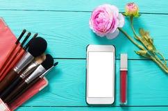 化妆产品和空白的流动屏幕框架在蓝色木背景 顶视图和拷贝空间 bird eye s speedwell 免版税图库摄影
