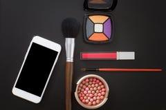 化妆产品和辅助部件在黑背景 空白移动电话屏幕 顶视图和拷贝空间 库存图片