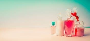 化妆产品横幅 在美好的桃红色土耳其玉色背景,正面图的另外化妆瓶罐收藏 免版税库存图片