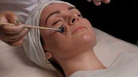 化妆刷子传播的奶油的特写镜头在一个美丽的女孩的面颊的 清洗的皮肤方法  影视素材