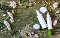 化妆容器瓶子浪花分配器绿色花白色老木背景国家边 免版税库存图片