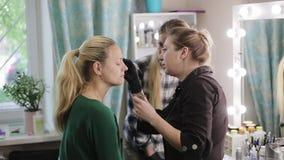 化妆师、学生和模型 学习的过程 新金发碧眼的女人 对俏丽的化妆师图画眼眉 股票视频
