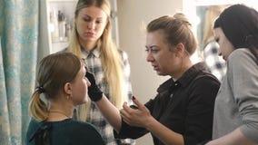 化妆师、学生和模型 学习的过程 新金发碧眼的女人 对俏丽的化妆师图画眼眉 影视素材