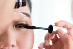 化妆师使用了与美丽的妇女的染睫毛油刷子 免版税图库摄影