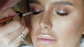 化妆师做在一名年轻好妇女的构成睫毛 股票录像