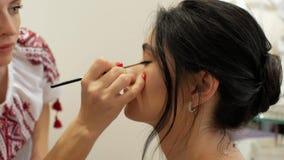 化妆师做构成一个美丽的深色的女孩 研究模型的图象的美发师 化妆师吸引眼睛与 股票录像