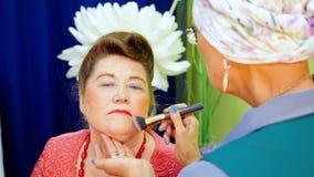化妆师做着资深妇女的构成 影视素材